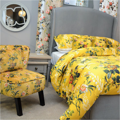 Matching yellow floral bed linens and accent chair